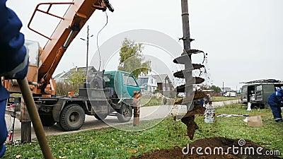 De kraan heft dienst voor kuilen onder bedradingspool aan op de kant van de dorpsweg stock videobeelden