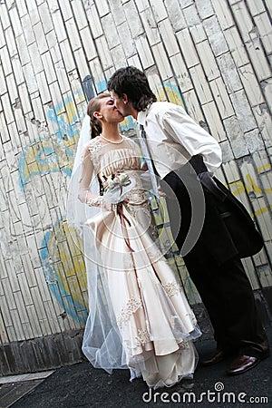 De kus van het huwelijk dichtbij de graffitymuur