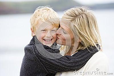 De kussende zoon van de moeder bij strand het glimlachen