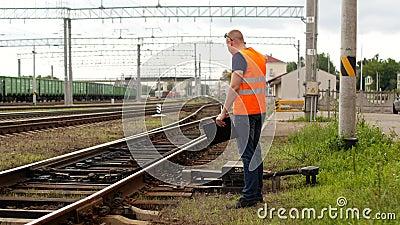 De kwade leider op de spoorweg inspecteert het mechanisme van de schakelaarspoorweg en gilt op de telefoon stock video