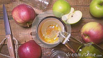 De la botella vierte el zumo de manzana fresco en vidrio Cámara lenta del estilo rústico almacen de metraje de vídeo