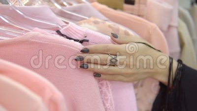 De langzame motie van vrouwen` s handen loopt over een rek van kleren, doorbladerend in een boutique stock video