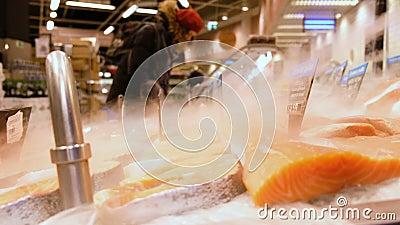 De lapjes vlees van rode vissen liggen braakakker in het ijs in een supermarktvitrine Op de achtergrond, kiezen de kopers product stock video