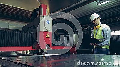 De lasermachine snijdt metaal onder de controle van de mannelijke werknemer stock video