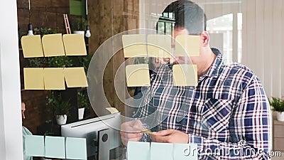 De leider die van het jonge mensenteam oplossing met zijn creatieve manager op kleverige nota's zoeken stock video