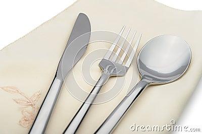 De lepel, de vork en een mes liggen op servet
