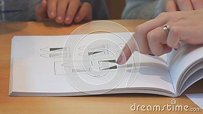 De leraar wijst een vinger naar de vormen in het geometrische handboek stock videobeelden
