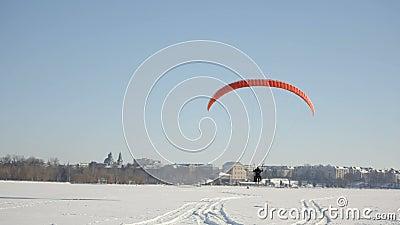 De loodsen van het glijscherm nemen in de lucht toe Concurrentie van glijschermen op het bevroren meer Ternopil de Oekraïne stock videobeelden