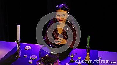 In de magische salon door kaarslicht, schuifelt een zigeuner fortunetelling kaarten stock footage