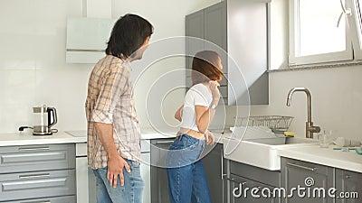 De man en de vrouw zijn gelukkig kopend een nieuwe flat De jonggehuwden in de keuken zijn gelukkig met nieuwe onroerende goederen stock video