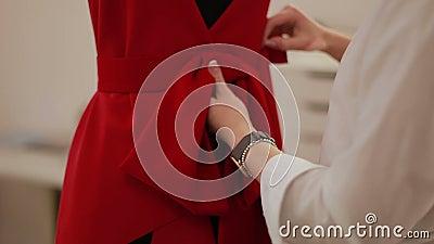 De manierontwerper kleedt maker die model in studio draperen Manierontwerper, kleermaker, naaister het aanpassen kleren