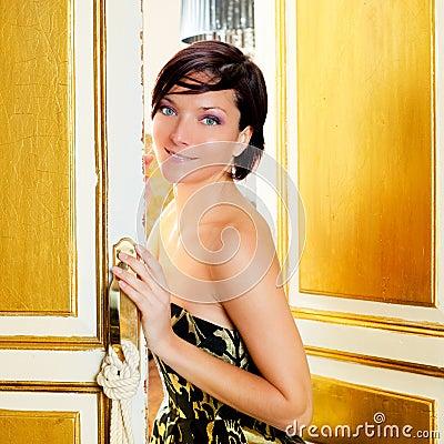 De maniervrouw van de elegantie in de deur van de hotelruimte