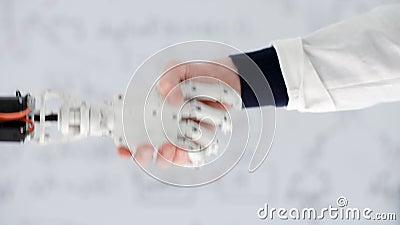 De mannelijke hand van artsenprosthetist schudt hand robotachtige prothese in medisch centrum stock footage
