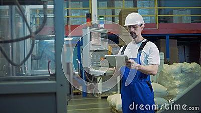 De mannelijke ingenieur met een tablet inspecteert industrieel vervaardigingsproces stock video