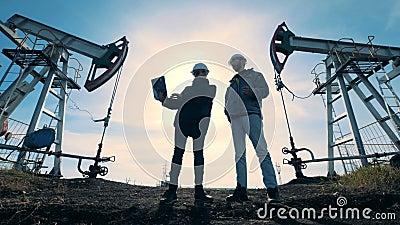 De mannelijke ingenieurs spreken terwijl status tussen brandstof pompende machines Energie, olie, gas, brandstof pompende install stock video