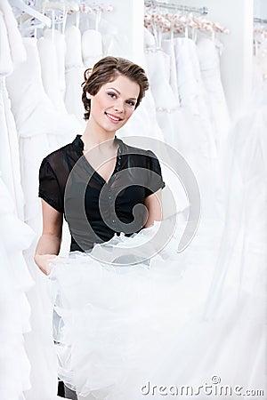 De medewerker van de winkel probeert om een juiste kleding te selecteren