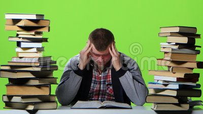 De mens die een handboek doorbladeren, het lijdt aan hoofdpijnen Het groene scherm stock videobeelden