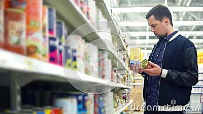 De mens in kruidenierswinkelopslag kiest ingeblikt voedsel Hij die zich dichtbij bevinden stock videobeelden