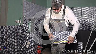 De mens met van de meterhulpmiddel en teller maatregel betegelt en maakt tekens op ceramische muurtegel stock videobeelden