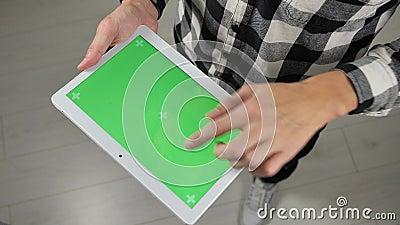 De mens staat op kantoor en houdt een digitale tablet vast met een chromakleurige groene schermtoets stock video