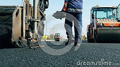De mens werkt op een weg met machines, met asfalt leggen stock video