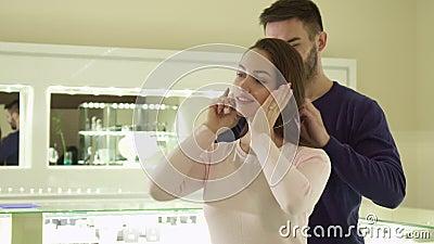 De mens zet de halsband op zijn meisje` s hals bij de boutique stock videobeelden