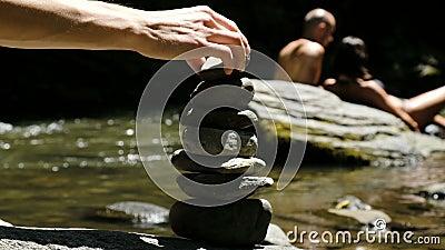 De mens zet een steenhoop die zich op een kei in een bergrivier tegen de achtergrond van toeristen bevinden stock videobeelden