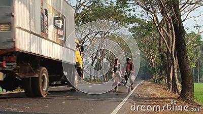 De mensen berijden fietsen door de weg in Jessore, Bangladesh stock videobeelden