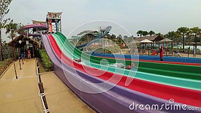 De mensen dalen van de kleurrijke waterdia's in Aqua Park van Ramayana thailand stock footage