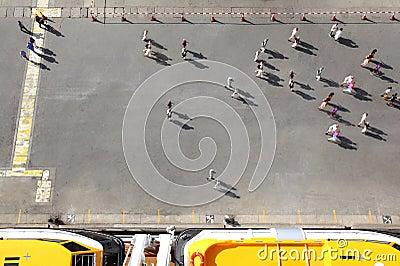 De mensen overbevolken unidirectionele beweging op werf dichtbij boten