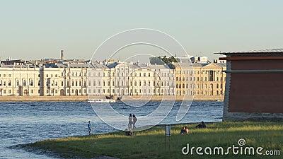 De mensen rusten op een kust van Peter en Paul Fortress in de zomer - St. Petersburg, Rusland stock footage