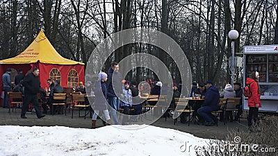 De mensen zitten bij lijsten in het stadspark en eten tijdens de vakantie Maslenitsa in BOBRUISK, WIT-RUSLAND 03 09 19 De burgers stock videobeelden