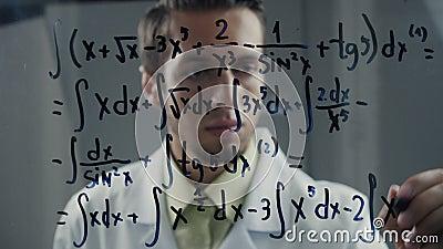 De mensenwetenschapper schrijft de integrale vergelijking op het glas Een wiskundige lost een wiskundig probleem op stock video
