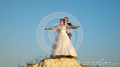 De de minnaarsbruid en bruidegom vliegen in dromen met wapens uitgestrekt tegen de blauwe hemel en de glimlach honeymoon romaans stock video