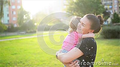 De moeder en het kind koesteren en hebben pret openlucht in aard, Gelukkige vrolijke familie Moeder en baby het kussen, het lache