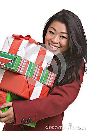 De mooie Aziatische vrouw draagt de giften van Kerstmis