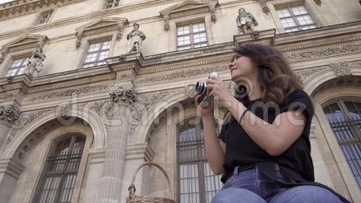 De mooie jonge vrouw met donker haar, die jeans en zwarte t-shirt dragen neemt beelden van de stad Linkerzijde aan juiste pan stock footage