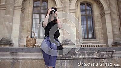 De mooie jonge vrouw met donker haar, die jeans en zwarte t-shirt dragen neemt beelden van de stad Recht op linkerpan stock video