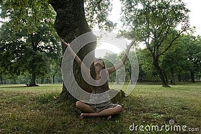 De mooie jonge vrouw zit onder een boom