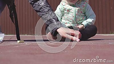 De mooie Kaukasische moeder trekt met kleurpotloden met haar weinig oude dochter 3 jaar op de speelplaats, spel stock footage