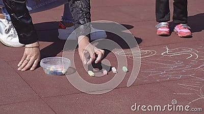 De mooie Kaukasische moeder trekt met kleurpotloden met haar weinig oude dochter 3 jaar op de speelse speelplaats, stock video