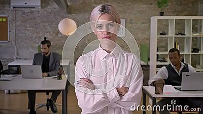 De mooie onderneemster bevindt zich en kruisend haar wapens in bureau, werken de collega's met laptops, het werkconcept stock video