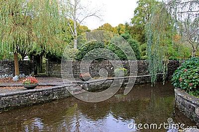 De mooie tuin van steenmuren mens maakte vijver bloemen en bomen stock foto afbeelding 48515173 - Foto van tuin vijver ...