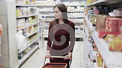 De mooie vrouw maakt het winkelen bij de supermarkt, steadicam schot stock video