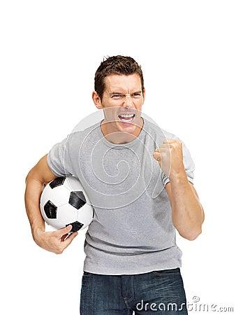 De opgewekte jonge ventilator die van het kerelvoetbal een voetbal houdt