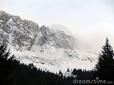 De pieken van de berg die door wolken en sneeuw worden behandeld
