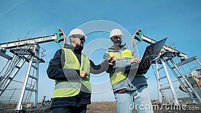 De plaats van de olieextractie met twee arbeiders die een gesprek hebben Werkende oliepompen, boorplatforms op een achtergrond stock footage