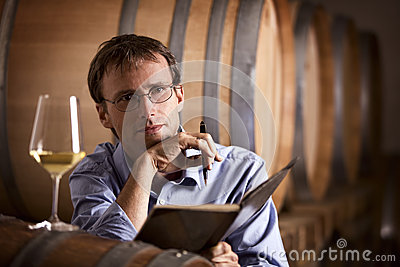 De producent die van de wijn in kelder overweegt.