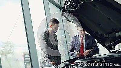 De professionele automobiele verkoper toont klantenmotor van een auto onder motorkap aan, bekijken de mensen autodelen stock videobeelden