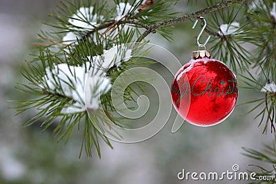 De rode decoratie van Kerstmis op snow-covered pijnboomboom in openlucht